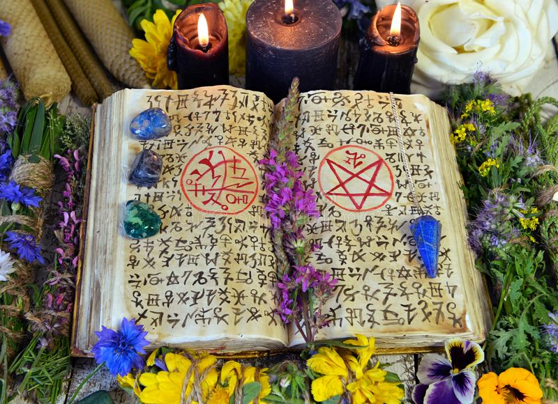 Witch book with spells and symbols, black candles, reiki crystals and flowers royalty free stock photos