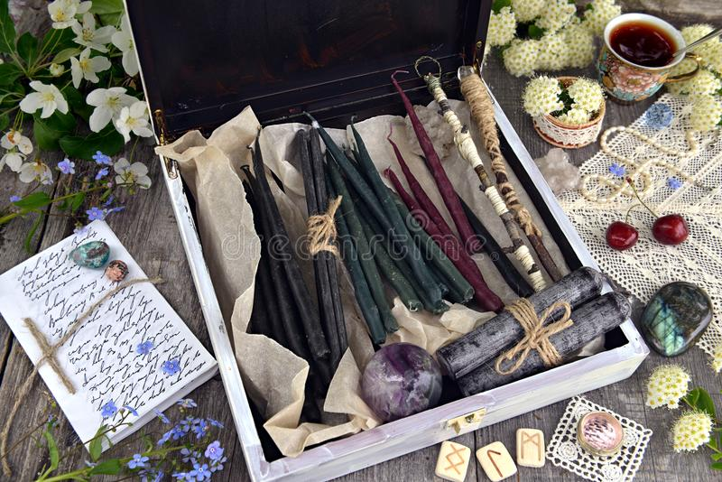 Witch box with hand made candles, crystal, runes, flowers and magic objects stock images