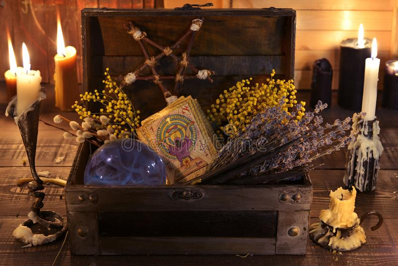 Witch box with healing herbs, crystal ball, tarot cards and burning candles. Wicca, esoteric, divination and occult background with vintage magic objects for royalty free stock photography