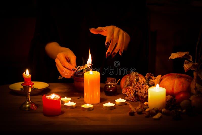 Witch bränner en ört på altaret i mörkret Honhänder med skarpa svarta naglar gör magi mellan ljus, pumpa, muttrar royaltyfria foton