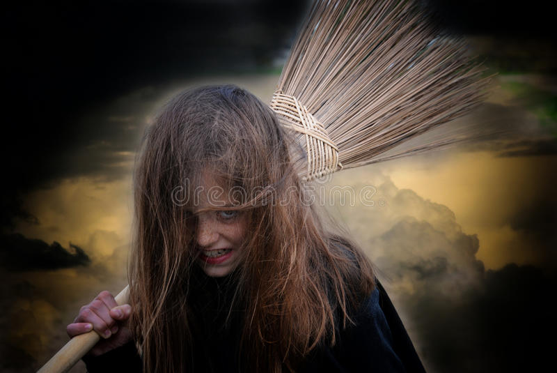 Witch with broom. Little witch with broom against dark sky royalty free stock image