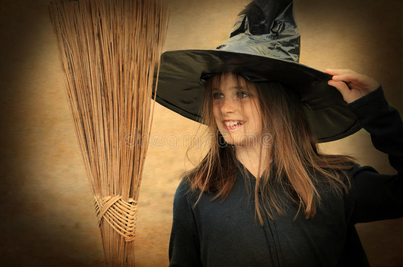 Witch with broom. Portrait of a little witch with broom royalty free stock photo