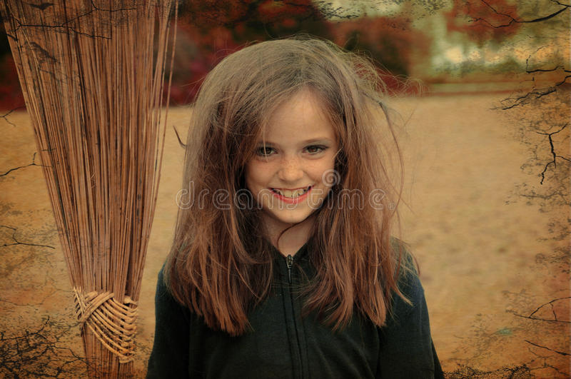 Witch with broom. Portrait of a little witch with broom stock photo