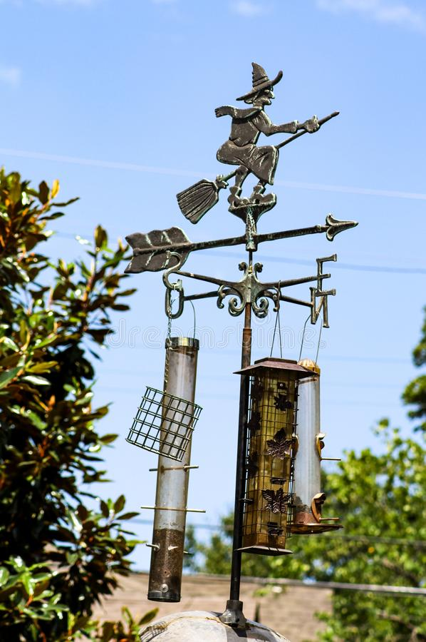 Witch on broom weather vane with bird feeders hanging from it stock photography