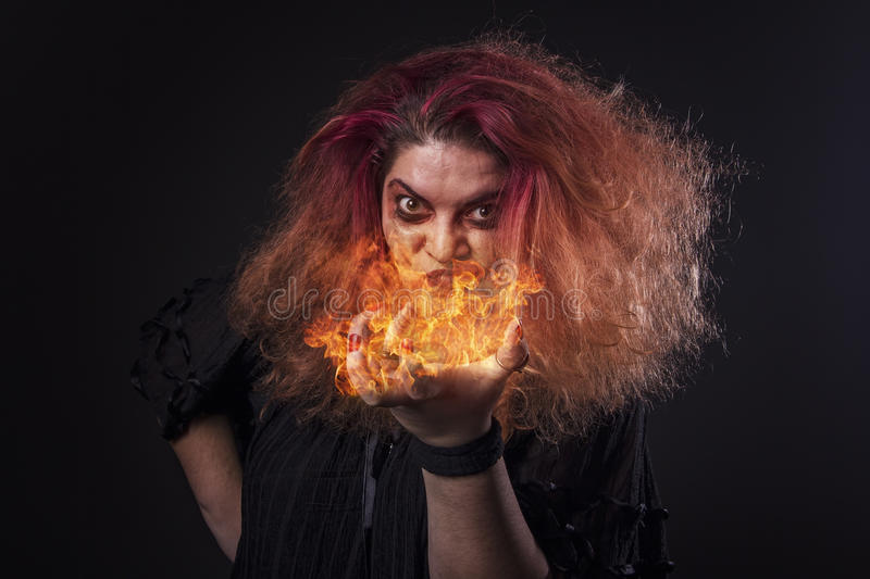 Witch casting a fire spell. Deranged horror girl with flame on her palm, casting spells, invoking spirits, fantasy scene royalty free stock photography