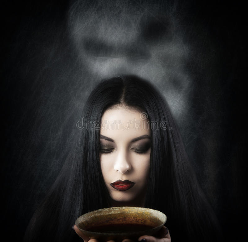 Witch with a cup of potion. Fantasy style portrait of a woman with a cup of potion stock images