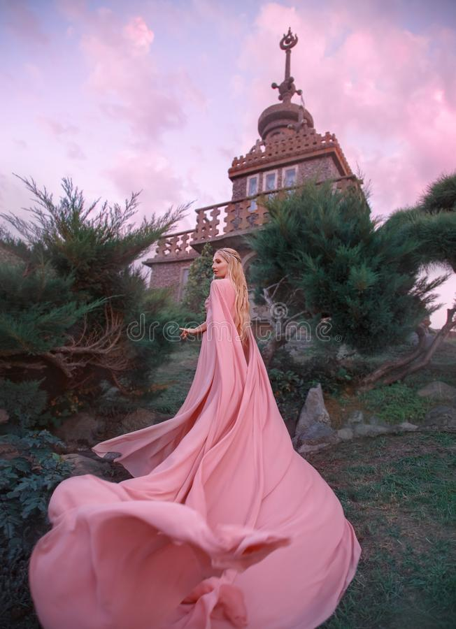 Witch elf rises to the castle, princess with blond hair, oblique and tiara dresses pink dress and cloak with a long. Train, curling with the wind, flies and royalty free stock photo