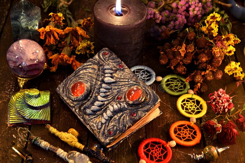 Witch grimoire with black candle, herbs and chakra decorations stock photography