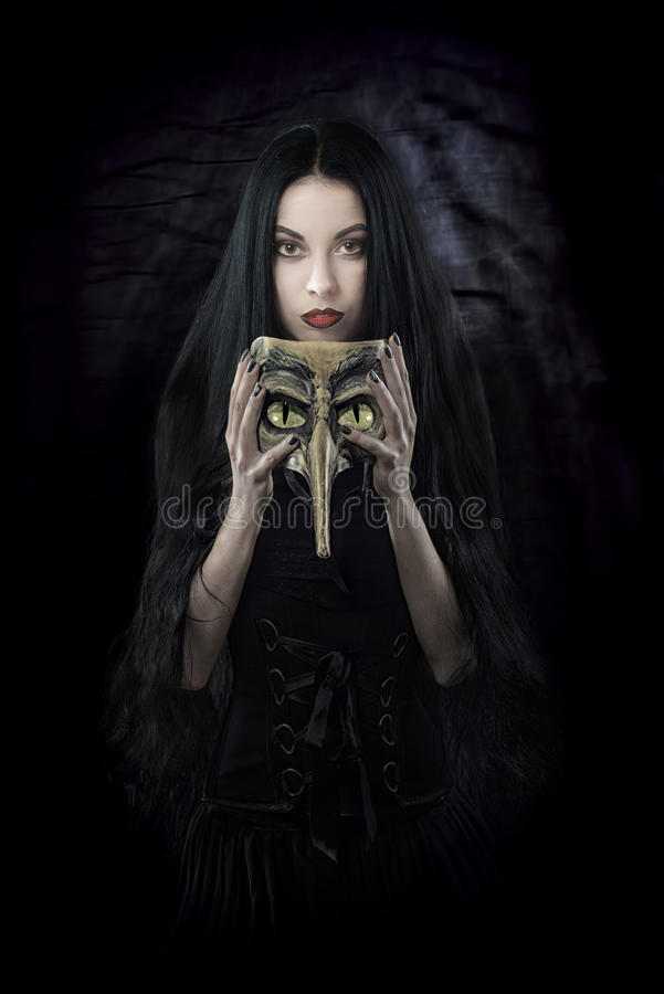 Witch holding a mask. Fantasy style portrait of a woman with a scary mask royalty free stock photography