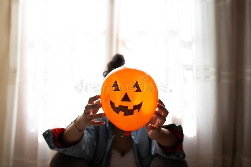 Witch holding a pumpkin balloon with her hands and covering her face. Young woman celebrating halloween. Helium party balloons stock photo