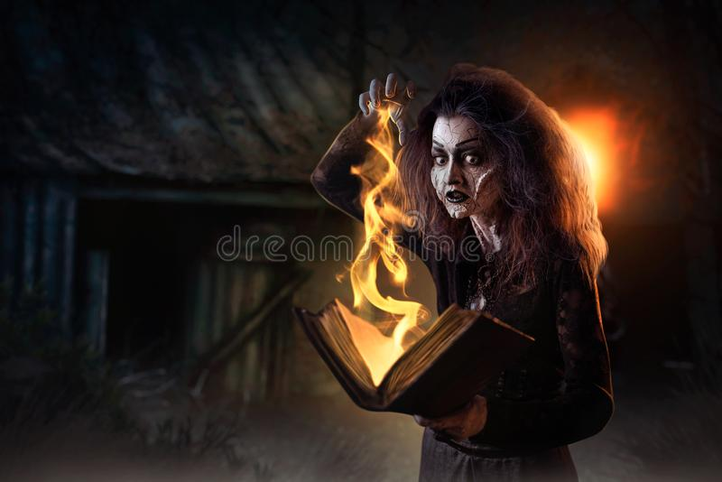Witch holds spellbook, dark powers of witchcraft. Scary witch holds spellbook, dark powers of witchcraft, spiritual seance. Female foreteller calls the spirits royalty free stock photos