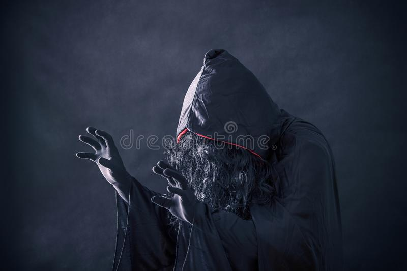 The witch in hooded cloak. In the darkness stock image