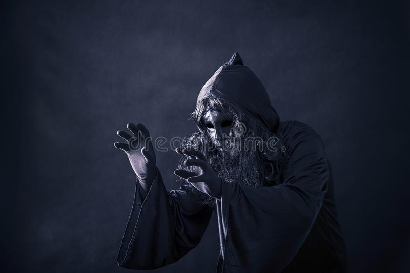 The witch in hooded cloak. In the darkness royalty free stock photography
