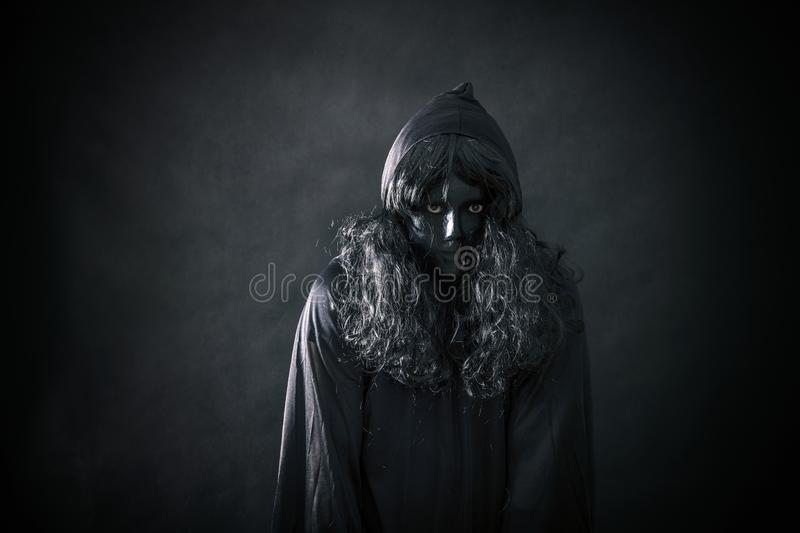 The witch in hooded cloak. In the darkness stock photos