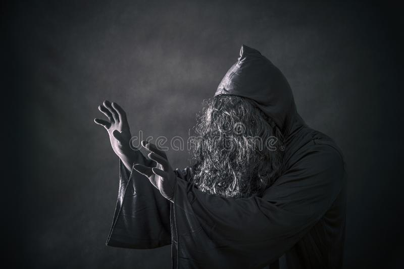 The witch in hooded cloak. In the darkness royalty free stock photo