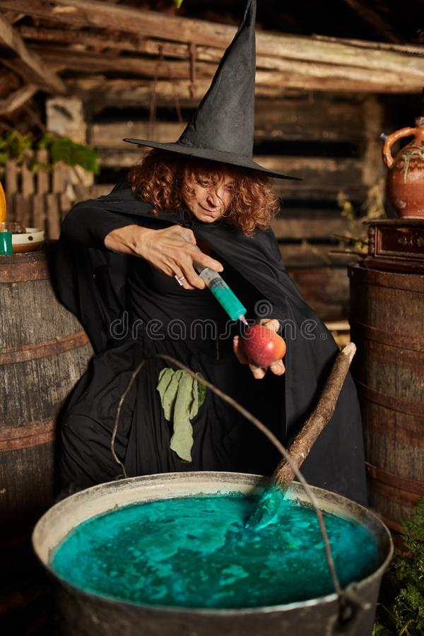 Witch injecting apple with poison stock photography