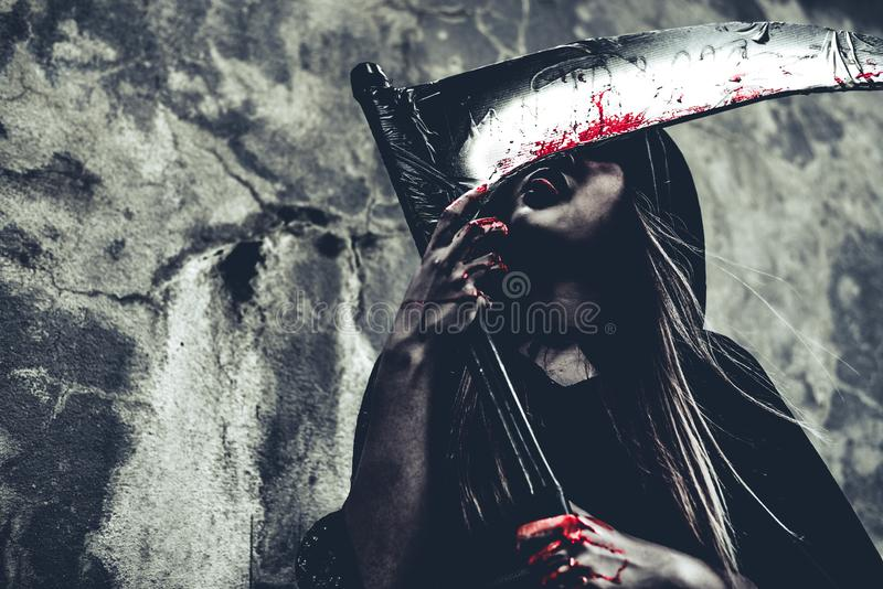 Witch licking blood on reaper. Female demon angel in black clothes and hood on grunge wall background. Halloween day and Mystery royalty free stock photography