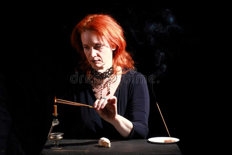 Witch light wizard candles. Fine emotional redhead witch with magical decorations and live expressions. Table with bird skull, candles and lamp. Black wizard stock photo