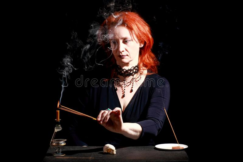 Witch light wizard candles. Fine emotional redhead witch with magical decorations and live expressions. Table with bird skull, candles and lamp. Black wizard royalty free stock photography