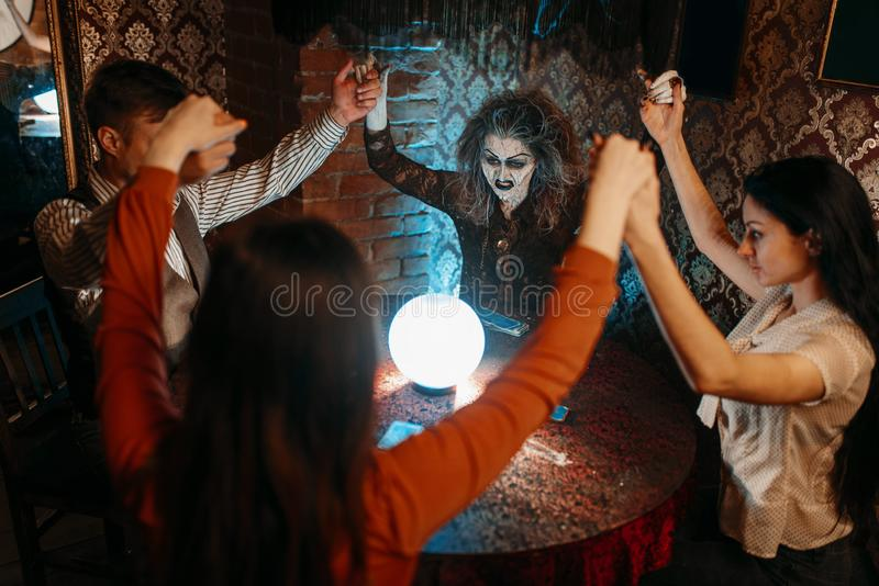 Witch over a crystal ball, young people on seance. Scary witch reads a magic spell over a crystal ball, young people hands up on spiritual seance. Female stock photography