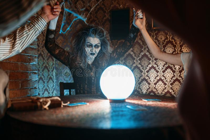 Witch over a crystal ball, young people on seance. Scary witch reads a magic spell over a crystal ball, young people hands up on spiritual seance. Female stock photo