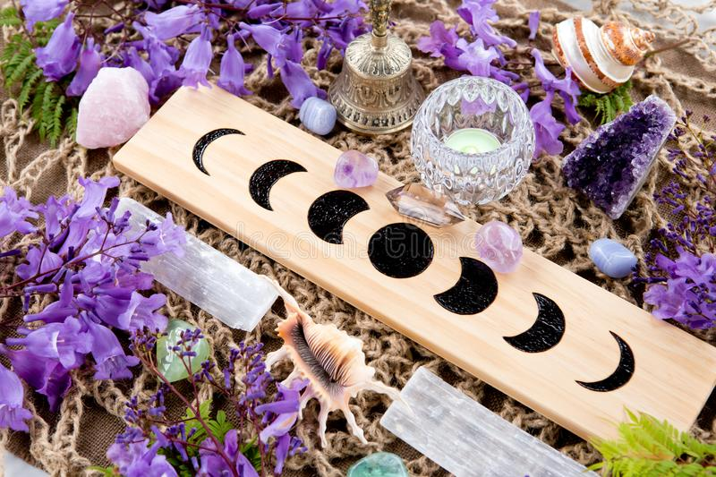 Witch Pagan Moon Phases Altar with crystals and flowers. Witch Pagan Moon Phases Altar with crystals of selenite and amethyst, with candle and purple flowers royalty free stock images