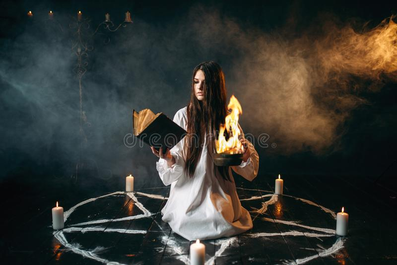 Witch in pentagram circle, dark magic ritual. Witch in white shirt sitting in the center of pentagram circle with candles, dark magic ritual process. Occultism royalty free stock image