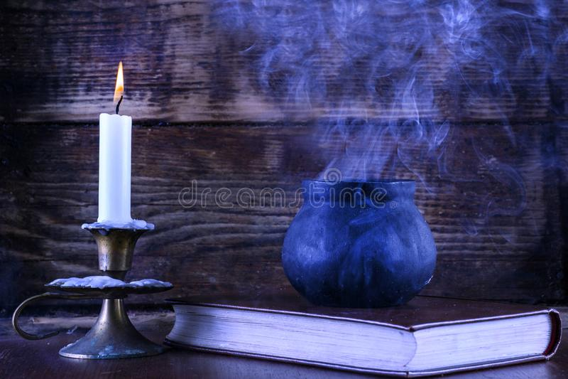 Witch pot on book of magic and candle with lit in candlestick. Old black witch pot on book of magic and wax candle with lit in candlestick burning. Smoke escapes stock photos