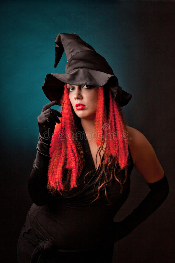 Witch practises witchcraft on black background. stock photos