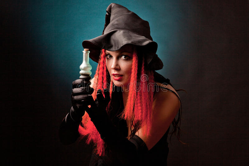Witch practises witchcraft on black background. stock image