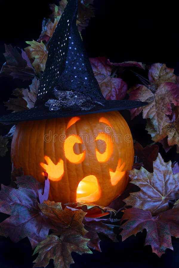 Witch Pumpkin. A frightened jackolantern dressed as a witch in a patch of leaves royalty free stock photos