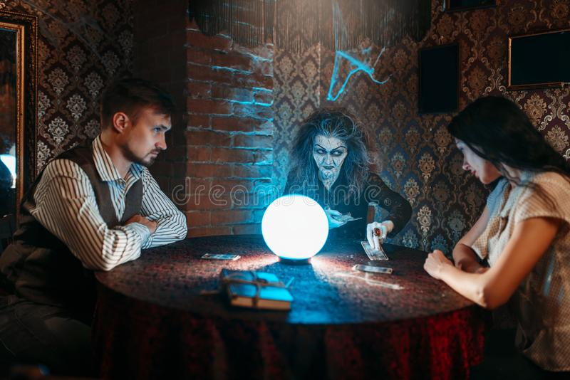 Witch reads a magic spell over a crystal ball. Young couple on spiritual seance. Female foreteller calls the spirits royalty free stock photo