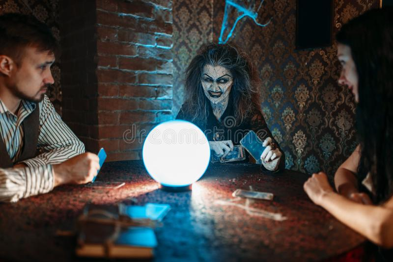 Witch reads a magic spell over a crystal ball. Young couple on spiritual seance. Female foreteller calls the spirits royalty free stock photos