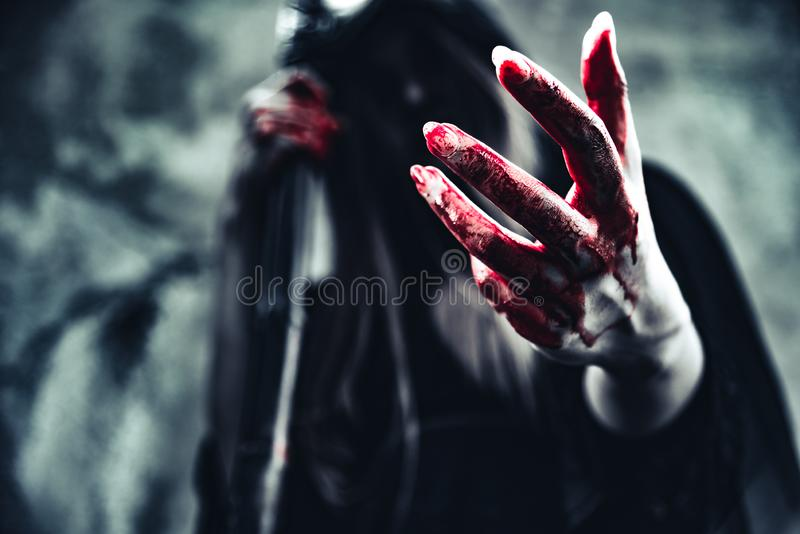 Witch showing bloody hand. Female demon angel in black clothes a royalty free stock photo
