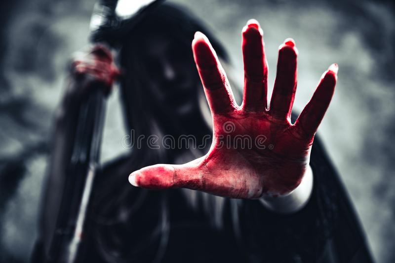 Witch showing bloody hand with reaper. Female demon angel in black clothes and hood on grunge wall background. Halloween day and. Mystery concept. Fantasy of stock image
