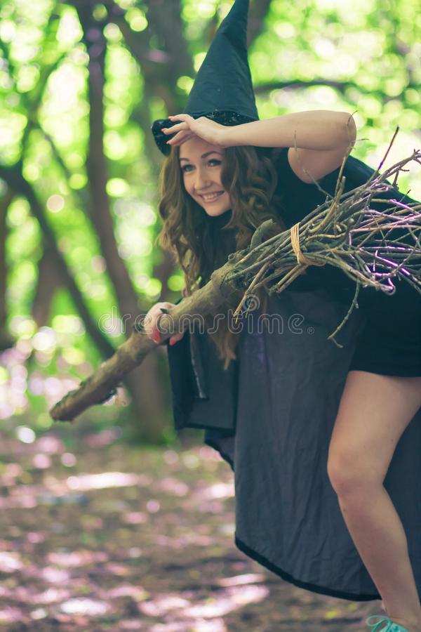 A witch student is preparing. To fly on a broom. an attractive girl in a witch`s hat stock images