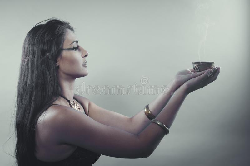 Witch, Tribute and prayer. Beautiful brunette with bronze bowl a royalty free stock images
