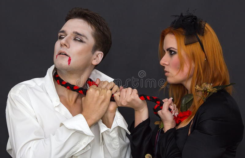 Witch and a vampire. On a dark background stock images