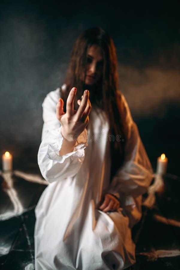 Witch calls upon the spirits, magic, witchcraft. Witch in white shirt calls upon the spirits, pentagram circle with candles, dark magic ritual process stock photos