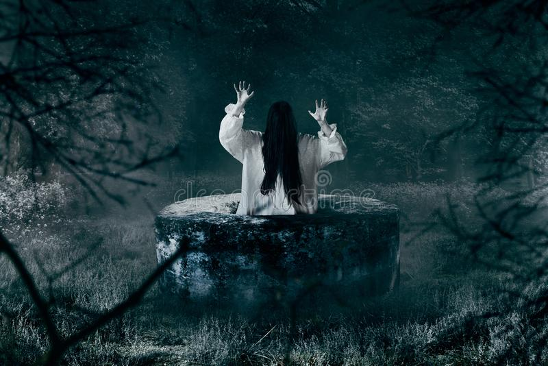 Witch in white shirt gets out of an abandoned well. In the night. Dark magic, occultism and exorcism, witchcraft royalty free stock photos