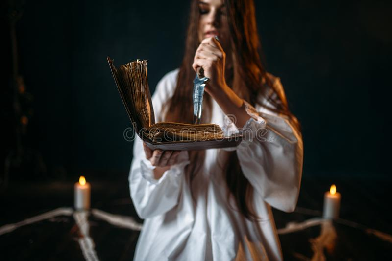 Witch in white shirt holds knife and reads spell. Pentagram circle with candles, dark magic ritual process. Occultism and exorcism stock image