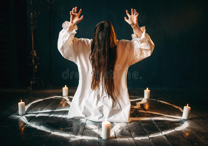 Witch produces occult ritual in pentagram circle. Witch in white shirt produses occult ritual in pentagram circle with candles. Dark magic ritual, occultism and royalty free stock images