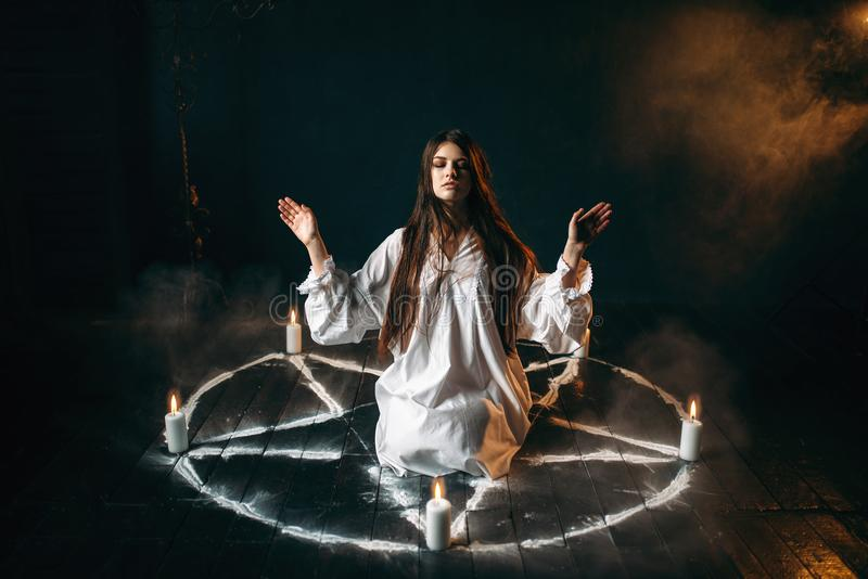 Witch in pentagram circle, evocation of spirits. Witch in white shirt sitting in the center of pentagram circle with candles, occult ritual, evocation of spirits stock image
