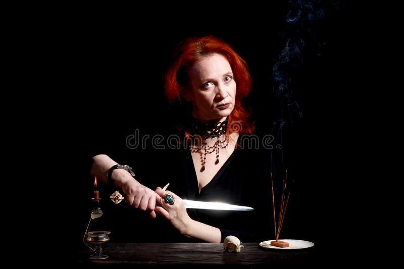 Witch with wizard stiletto. Fine emotional redhead witch with magical decorations and live expressions. Table with bird skull, candles and lamp. Black wizard stock photography