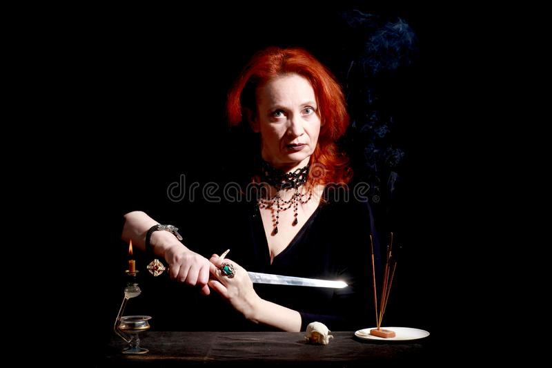 Witch with wizard stiletto. Fine emotional redhead witch with magical decorations and live expressions. Table with bird skull, candles and lamp. Black wizard royalty free stock photo