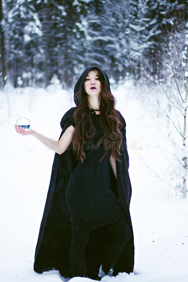 Witch or woman in black cloak with glass ball in white snow forest. Witch or woman in black cloak with glass ball in snow forest stock photo