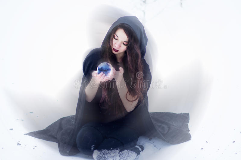 Witch or woman doing magic in black cloak with glass ball in white snow forest. Witch or woman doing magic in black cloak with glass ball in snow forest stock photography