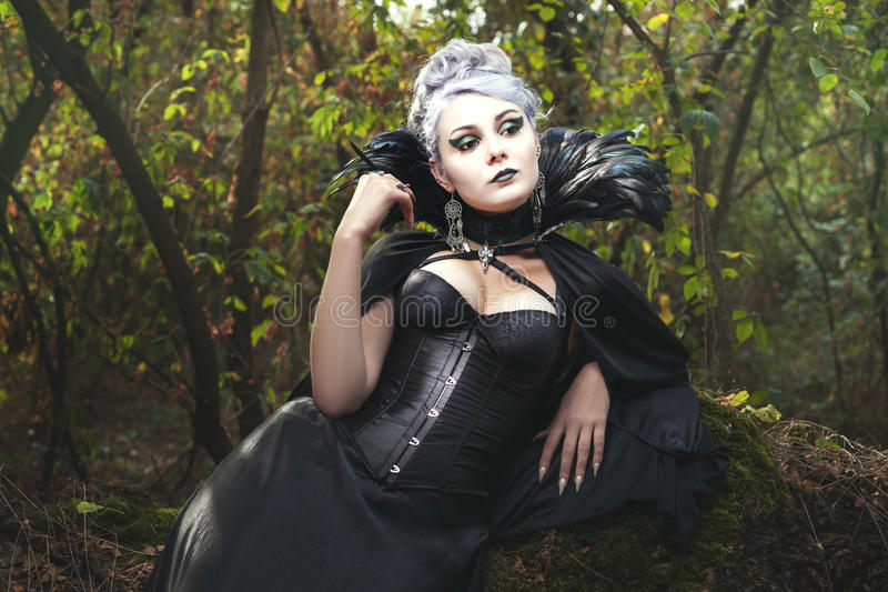 Witch in the woods. Beautiful woman a witch in the dark forest royalty free stock photography