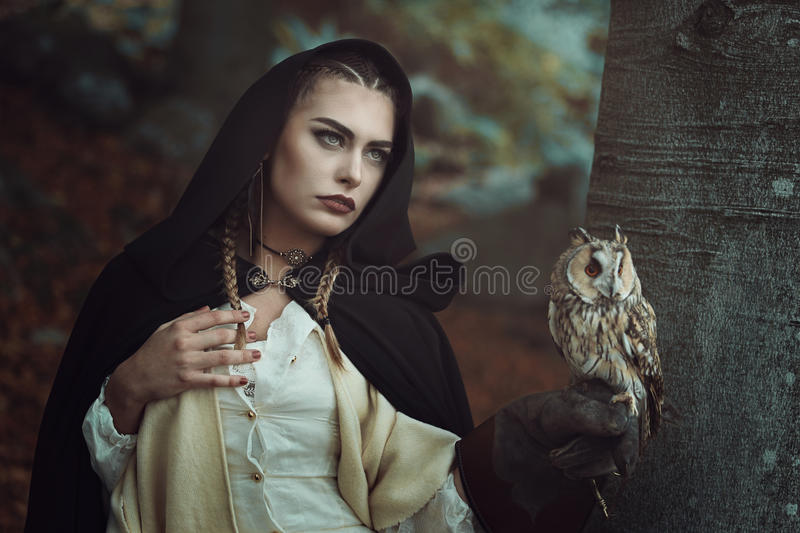 Witch of the woods with her owl stock photos