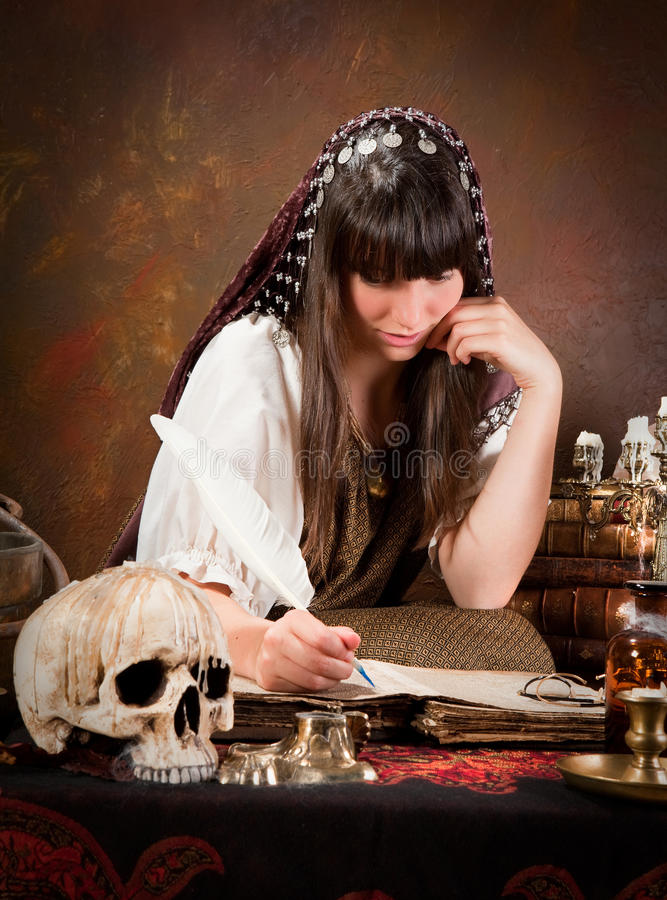 Witch writing in the book of shadows stock image